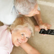 Happy old couple watching televison together - Stock Photo