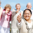 Royalty-Free Stock Photo: Old female showing thumbs up sign with her friends
