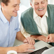 Royalty-Free Stock Photo: Father and son smiling while working on laptop