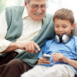 Royalty-Free Stock Photo: Old man sitting with his grandson listening to music