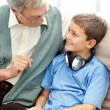 Old man sitting with his grandson wearing a headphone - Foto Stock