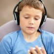 Cute little boy listening to music on the mp3 player - Foto Stock