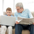 Old man sitting with a newspaper while a little boy using a lapt - Stock Photo