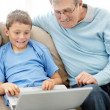 Little boy and his grandfather sitting together using a laptop - Foto Stock
