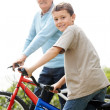 Royalty-Free Stock Photo: Smiling young boy and his grandfather on bicycles