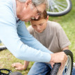Royalty-Free Stock Photo: Old man repairing his grandson \'s cycle in a park