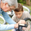 Royalty-Free Stock Photo: Senior man repairing a bicycle tyre with his grand son