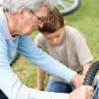 Royalty-Free Stock Photo: Elderly man repairing his grandson \'s cycle in a park