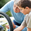 Royalty-Free Stock Photo: Little boy and his grand father rapairing a cycle