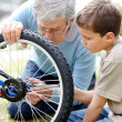 Royalty-Free Stock Photo: Aged man repairing a bicycle tyre with his grand son