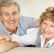 Happy old couple looking behind while sitting on sofa - 