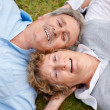 Royalty-Free Stock Photo: Loving senior couple lying on ground smiling