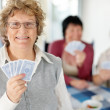 Old woman holding playing cards with at the back - Stock Photo