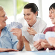 Smiling mature woman with old playing cards - Stockfoto