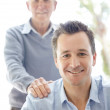 Royalty-Free Stock Photo: Handsome young man with his father standing in background