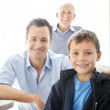 Royalty-Free Stock Photo: Cute small boy smiling with his father and grandfather