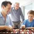 Royalty-Free Stock Photo: Little boy enjoys a game of backgammon with his father