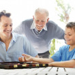 Royalty-Free Stock Photo: Happy family playing together a game of backgammon