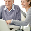 Lovely young female using laptop with her father - Foto Stock