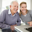 Happy young woman working on laptop with her father - Foto Stock