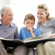 Royalty-Free Stock Photo: Happy family sitting together and reading a book - Indoor