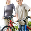 Royalty-Free Stock Photo: Happy young mother and son standing with bicycle