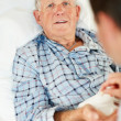 Royalty-Free Stock Photo: Elderly man receiving pill from the doctor