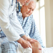 Doctor checking old man knee using a reflex hammer - Stock Photo