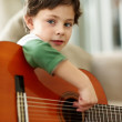 Royalty-Free Stock Photo: Young boy playing acoustic guitar at home