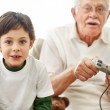 Royalty-Free Stock Photo: Boy and his grandfather with video game controllers