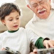 Royalty-Free Stock Photo: Little boy helping his grandfather while playing video game