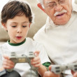Royalty-Free Stock Photo: Old man and his grandson playing video game at home