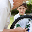 Royalty-Free Stock Photo: Little boy watching a old man fix a bicycle tyre
