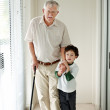 Royalty-Free Stock Photo: Small boy helping a old man on walking stick