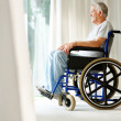 Disabled old man on wheelchair looking outside - Foto Stock