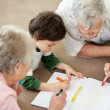 Royalty-Free Stock Photo: Old couple helping their grandson in making a drawing
