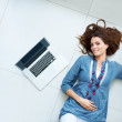 Charming young female lying on the floor with laptop - Stock Photo