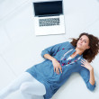 Young woman relaxing on the floor with laptop - Stock Photo