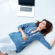 Happy young woman lying on floor by laptop - Stock Photo