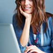 Charming young woman working on laptop - Stock Photo