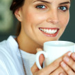 Happy young woman drinking a cup of coffee - Stock Photo