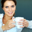 Beautiful young woman holding a cup of coffee - Stok fotoraf
