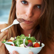 Be vegetarian - Beautiful young woman eating fruit salad - Стоковая фотография