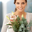 Attractive brunette holding bunch of flowers - Stock Photo