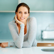 Relaxed young woman standing at the kitchen counter - Foto de Stock  