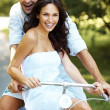 Royalty-Free Stock Photo: Attractive young couple on bike in a park