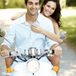 Young couple riding on moped in a park - Stock Photo