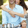 Royalty-Free Stock Photo: Happy young love couple on a scooter in a park