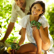 Happy young couple gardening outdoors smiling - Stock Photo