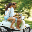 Royalty-Free Stock Photo: Young love couple enjoying ridding on scooter